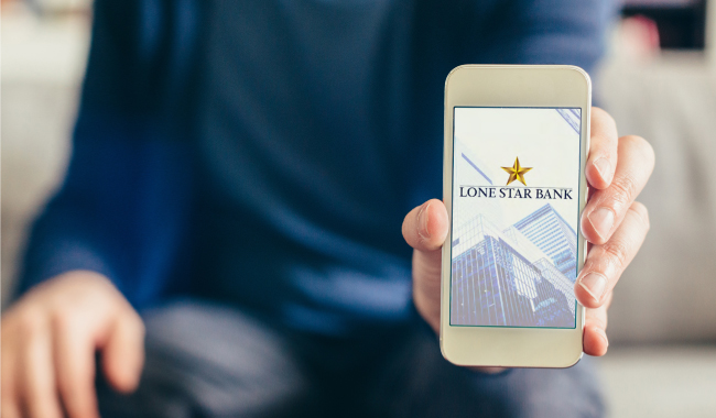 A person holding a mobile phone with the Lone Star Bank mobile app on screen